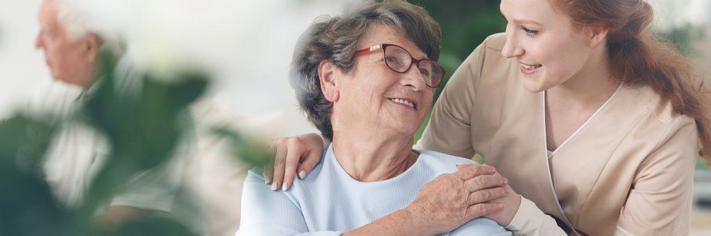 Professional,Helpful,Caregiver,Comforting,Smiling,Senior,Woman,At,Nursing,Home